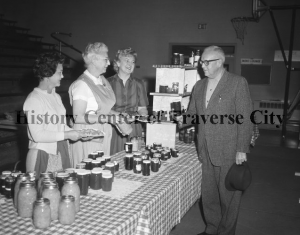 Gretchen (Arntz) Votruba, in the apron, at a St. Francis Bazaar selling canned goods. Gretechen was active in the Salvation Army and Child and Family Services and later at the Dennos Museum, ca. 1940s. Image courtesy of the History Center of Traverse City.