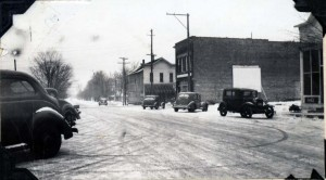 Downtown Kingsley in the 1930s. The building furthest away, north of M113, was Hooper's tavern, where Katy's folks first lived when they moved to Kingsley. The Cleland Tavern, where movies were shown on the painted screen on the building's side, is now where the auto supply store sits. Image courtesy of the Floyd Webster Historical Photograph Collection, http://localhistory.tadl.org/items/show/605