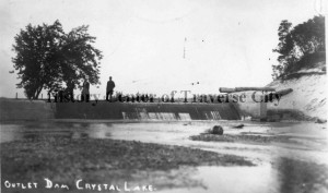 Crystal Lake outlet dam with three people standing in the lake (ca. 1920). Image courtesy of History Center of Traverse City.