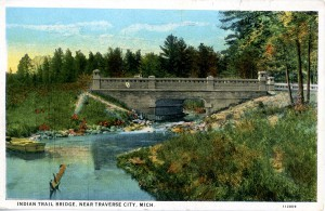 "This colored postcard image depicts Indian Trail Bridge, which was actually Mitchell Creek bridge on the West Michigan Pike in Traverse City. This section was called ""Hamilton Way"" after Frank Hamilton who was very dedicated to the development of roads in this area. The Indian Trail Camp Tourist hotel frequently had a sign up at this bridge, which may be why the creators called this image ""Indian Trail Bridge"". Image courtesy of Traverse Area District Library."