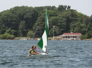 Onekama Sailing Club in August 2014, right. High school juniors Sarah and Katie race to the finish last year, but lost to Bob Beal by one-half of a second.