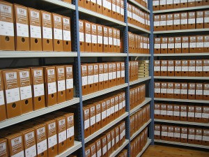 Shelved record boxes at an archive. Image courtesy of Depósito del Archivo de la Fundación Sierra-Pambley, through Wikimedia Commons.
