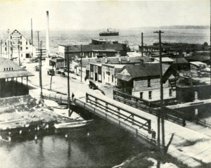 "Overview of the north Union Street bridge over the Boardman River taken from the tower of the Traverse City State bank. Steamer ""Puritan"" on the bay, ca. 1910-20. Image courtesy of Traverse Area District Library, Local History Collection."