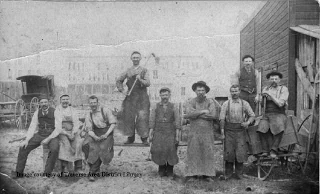 Victor Petertyl Wagon Works employees at the factory on State Street, 1891. (Note the Hannah Lay store on Front street in the background with almost nothing between them.) L-R: Vic Petertyl, Jim ? (woodworker), Wm. Abbott (horse shoer), Herman Koch (finisher), Albert Petertyl (blacksmith), Vencil Sleder (woodworker), Pat Robertson (helper and horse shoer), Chas. Weland (painter) and Anton Petertyl. (At the far left is either the Union Street Hotel or the back of the Masonic Building. Opinions vary.) Perhaps a member of the Sleder family can inform us the relationship between Vencil and Vaclav. From the Photo Collection at Traverse Area District Library Local History, 718.000001.100.