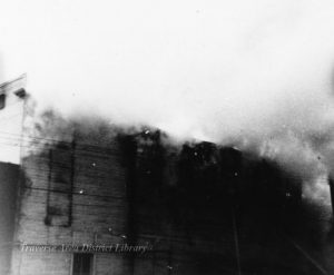 Image of the 1896 fire, actively burning frame buildings on the north side of Front Street. From the Local History Collection, Traverse Area District Library.